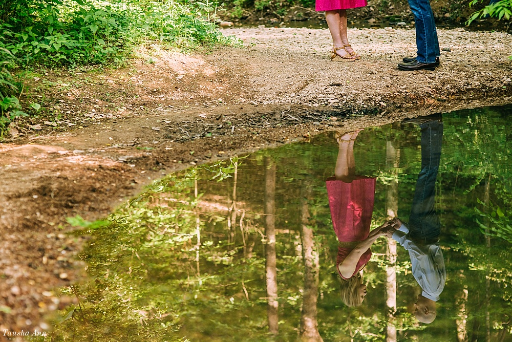 Reflection of engaged couple in stream at Percy Warner Park in Nashville TN