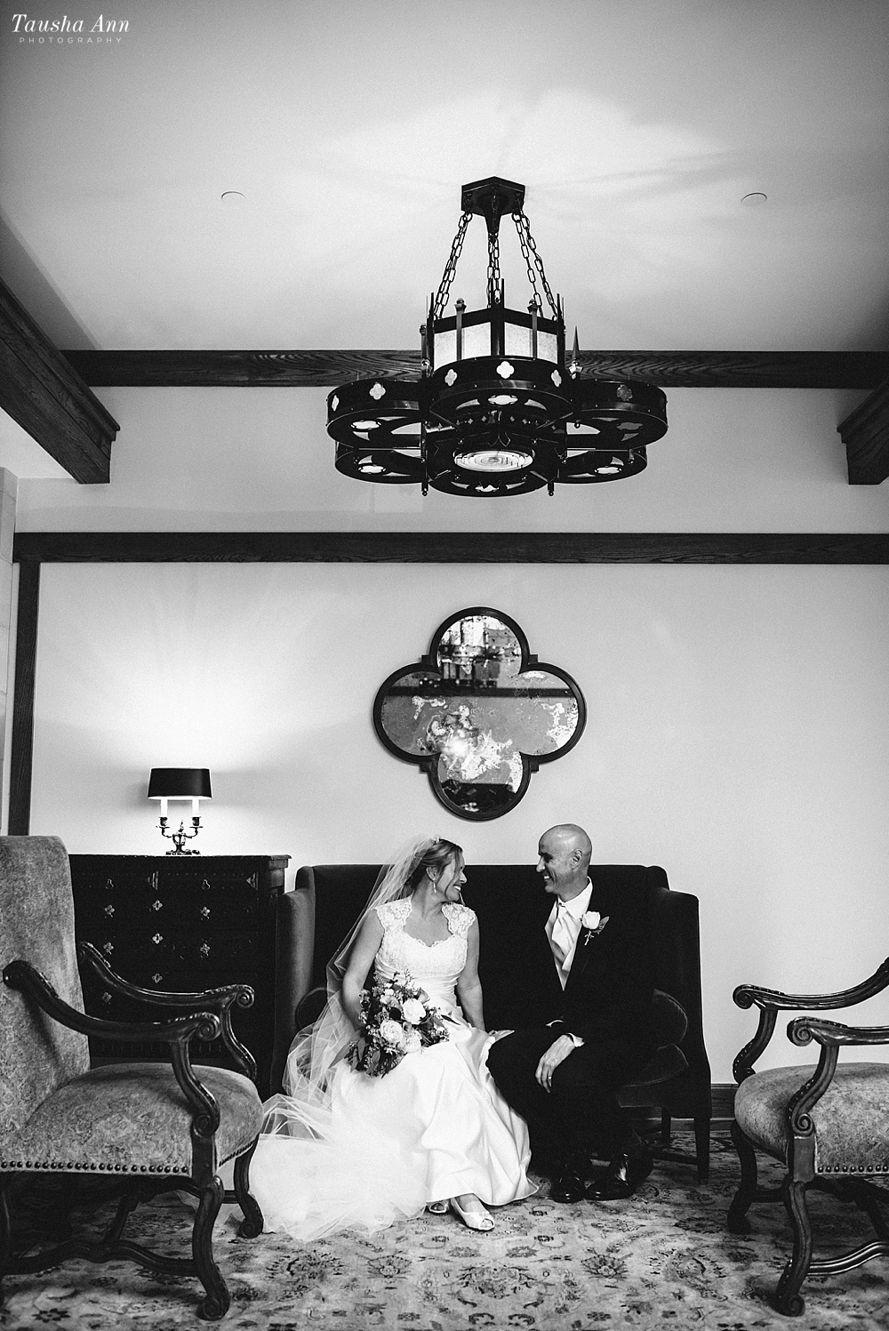 Portraits of Bride and Groom in Black and white sitting on couch with epic lighting fixture