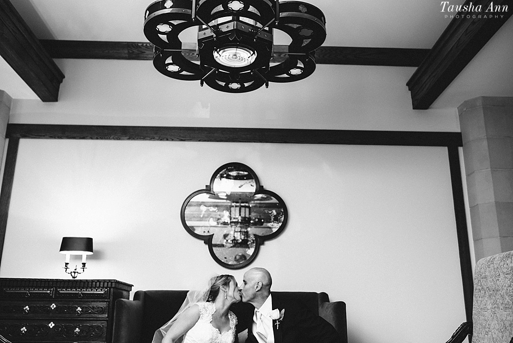 Black and White Portrait of Bride and Groom in Black and white sitting on couch with mirror