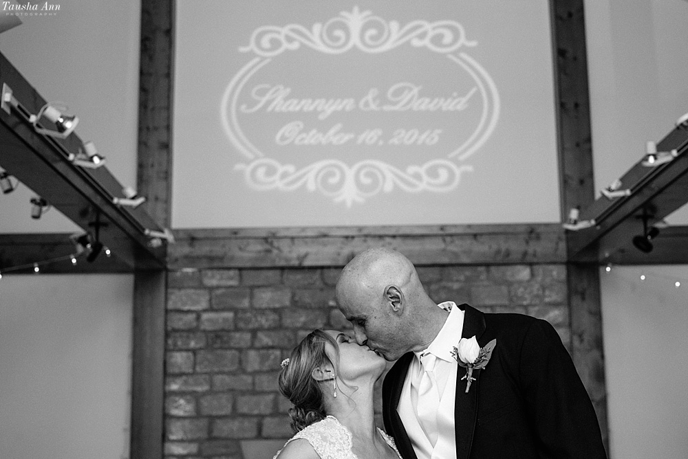 Bride and Groom kissing under sign that says Shannyn & David October 16, 2015