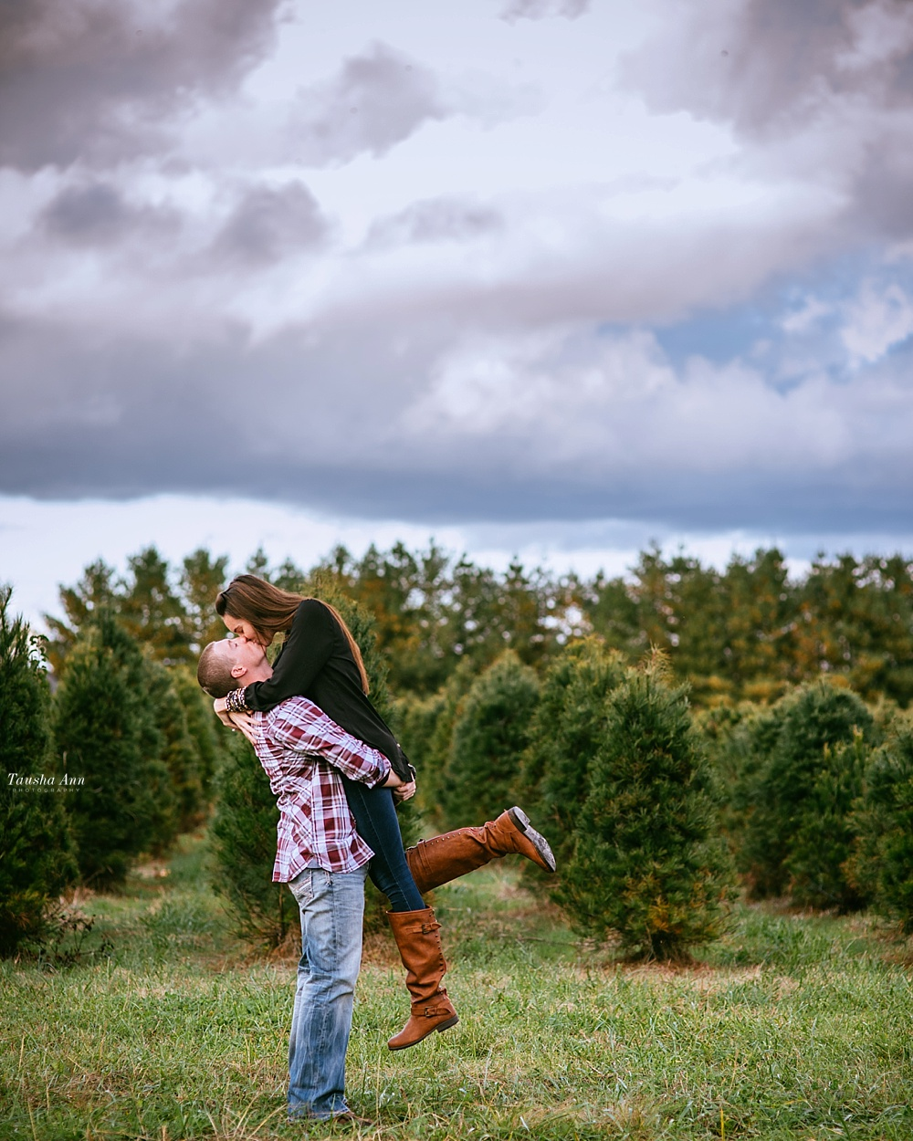 Surprise Proposal at Country Cove Christmas Tree Farm. Kissing, backlit by the sun and beautiful cloudy sky. Picking girl up. Foot kicked back.