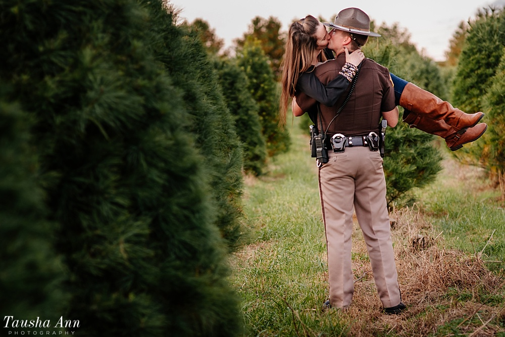 Surprise Proposal at Country Cove Christmas Tree Farm. Police officer surprise proposal at Sunset. Holding girl and kissing her in between Christmas Trees.