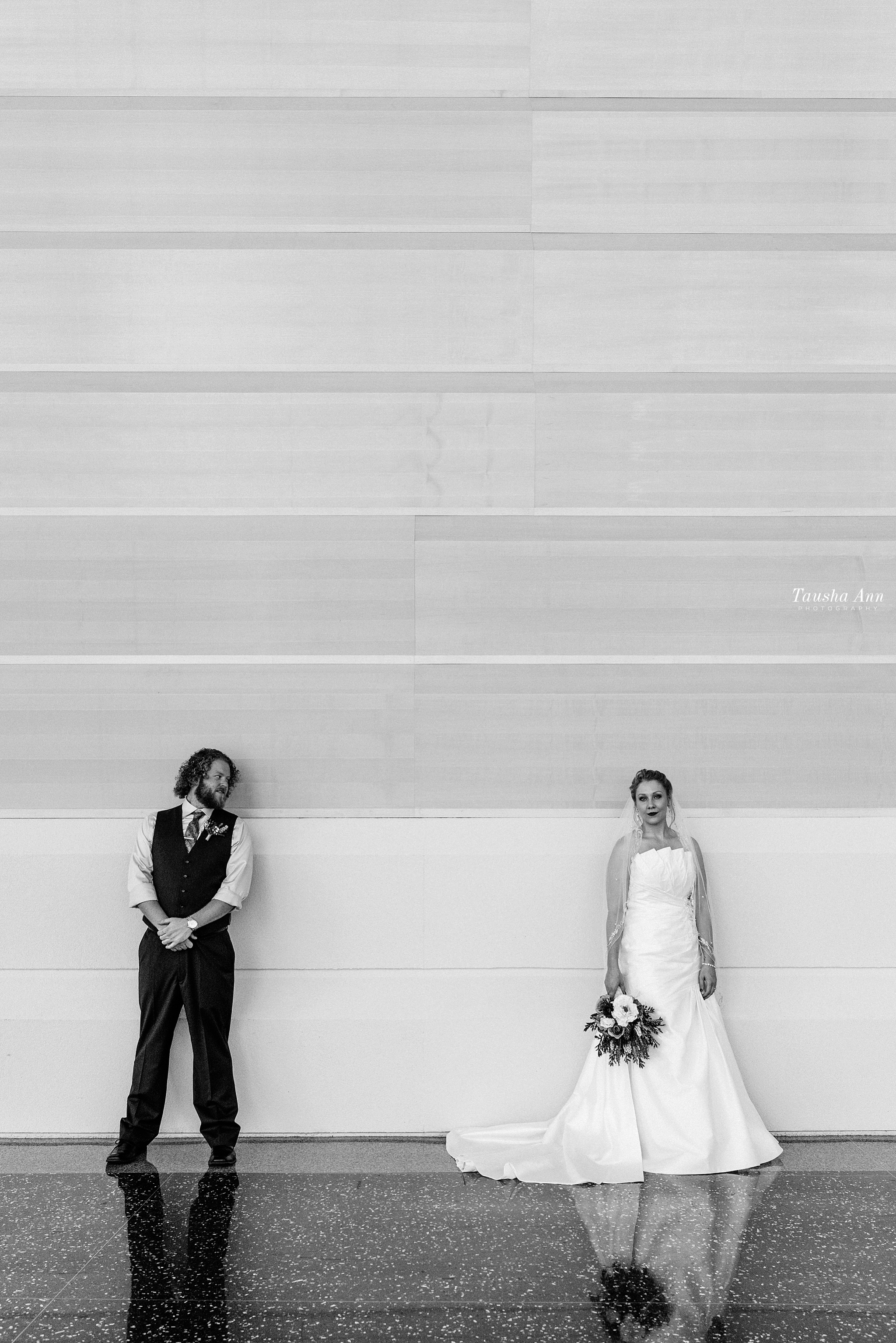 Bride and Groom standing up against wall. Groom looking at bride. Bride looking at camera. Grand Wayne Convention Center. Black and White.
