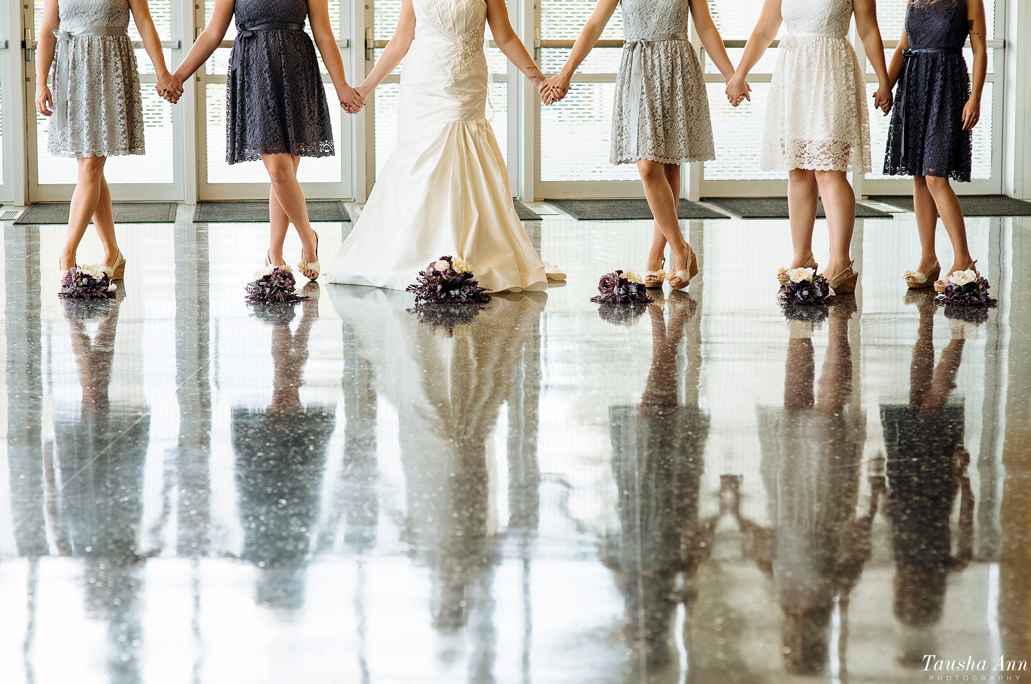 Bride and Bridesmaids holding hands with feet crossed. Showing reflection off of the ground. Grand Wayne Convention Center.