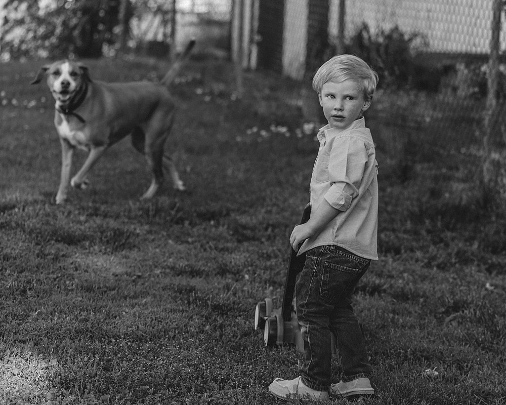 B&W Boy mowing lawn with toy lawn mower in backyard with dog