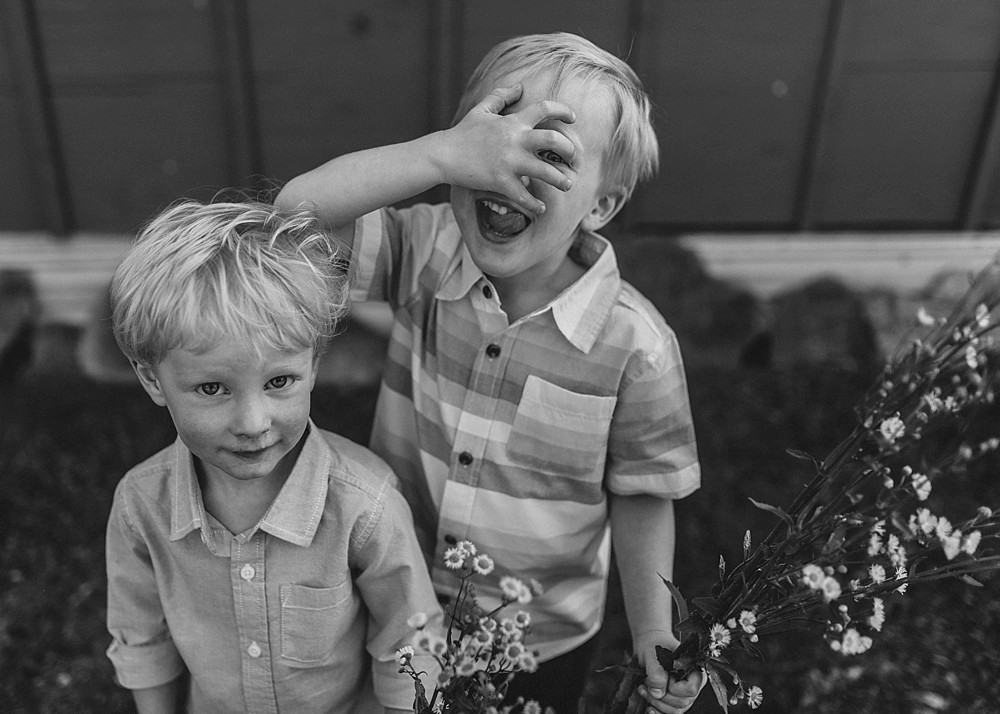 Boys being silly, lifestyle photography, with weeds and flowers, sticking tongue out, Black and White