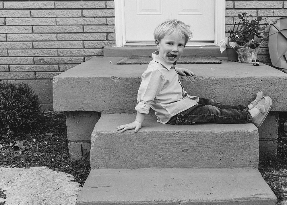 Boy sitting on steps sticking out tongue, black and white lifestyle photography