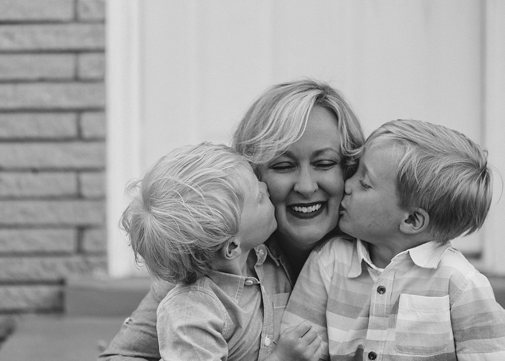 Little boys kissing their mom on the cheek.