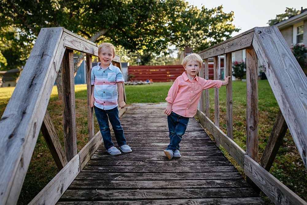 Boys standing on wooden bridge in backyard, real life