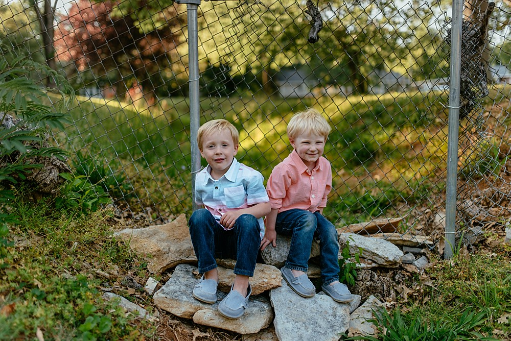 Boys sitting on a pile of rocks in their back yard, metal fence, Smiling