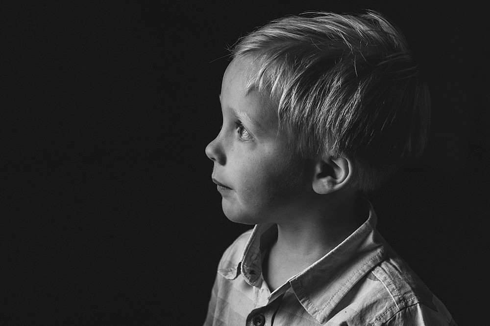 Black and White portrait of boy, black backround