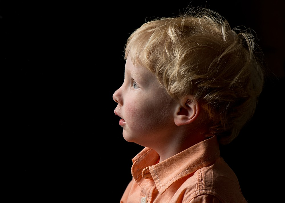 Portrait of toddler, black background, looking into the light.