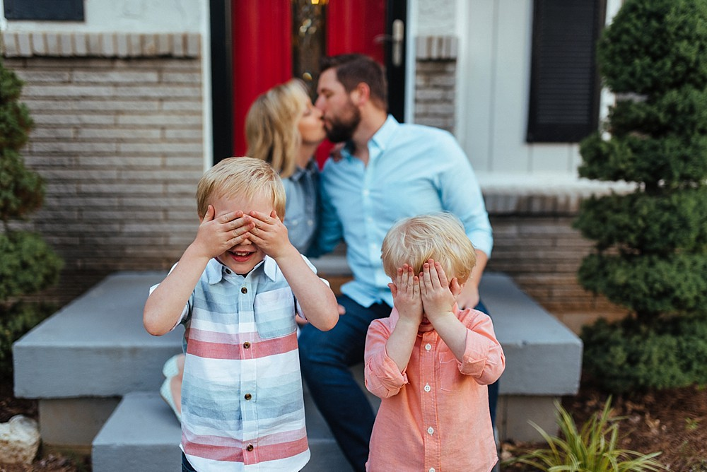 Young family on front porch, parents kissing and little boys covering their eyes