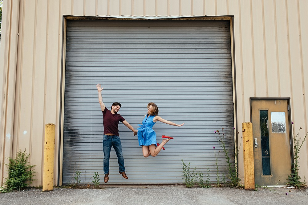 Couple against garage doors - jumping - fun - Nashville-Wedding-Photographer-Engagement_Photos_Downtown_Franklin_TN_Tausha_Ann_Photography_0006