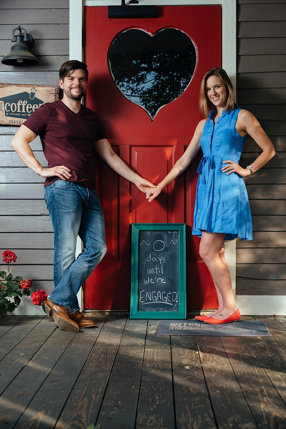 Couple with a sign and red door with heart - Nashville-Wedding-Photographer-Engagement_Photos_Downtown_Franklin_TN_Tausha_Ann_Photography_0006