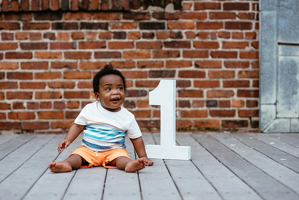One year old sitting in orange shorts and striped shirt with a number 1 wooden sign next to him with brick in the background