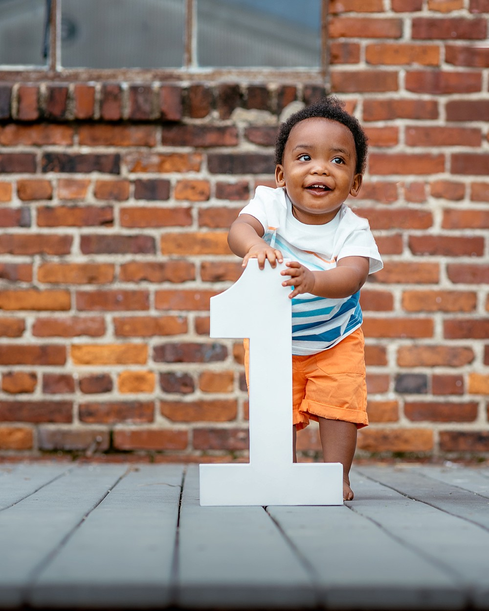 toddle standing holding onto his white one year old wooden sign. Brick in the background.