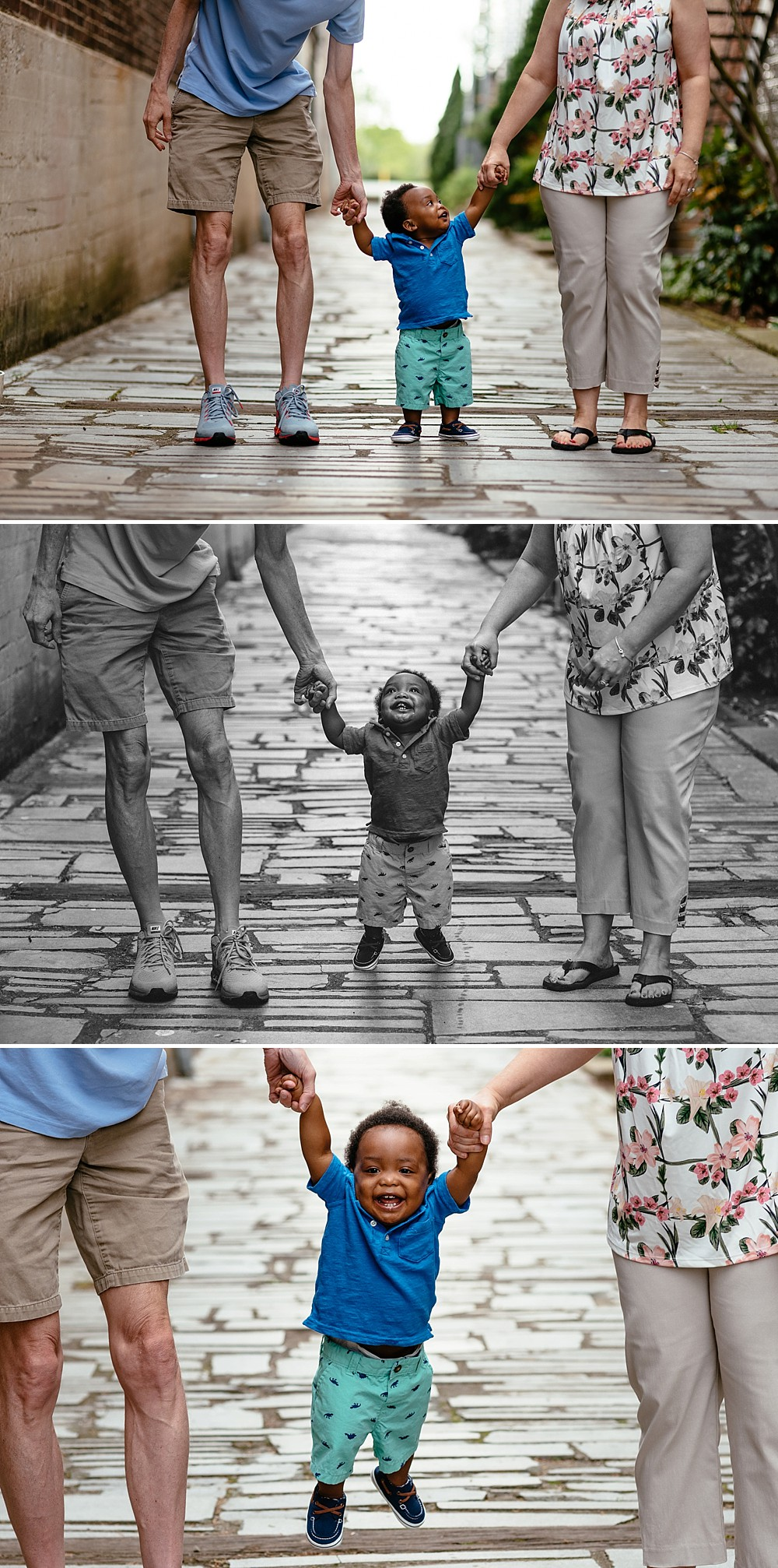 one year old looking up to his parents holding their hands and smiling