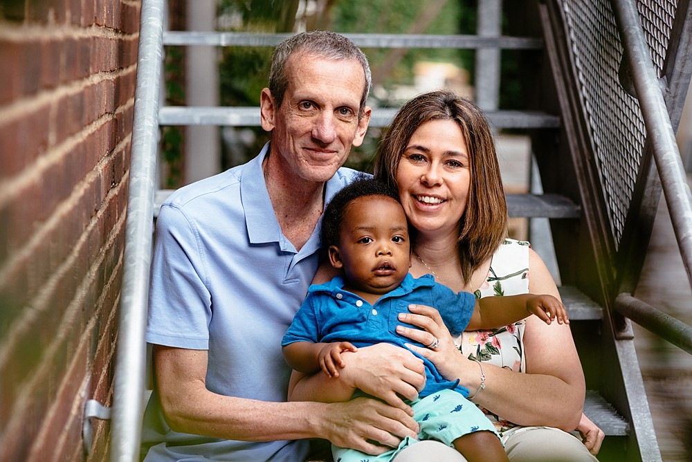 Happy family of three family photo sitting on metal stairs with red brick on the side