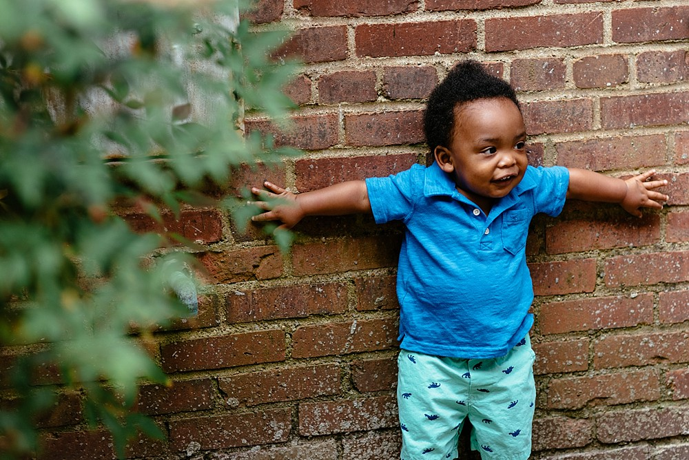little boy wearing green golf shorts and blue polo being silly standing up against brick wall