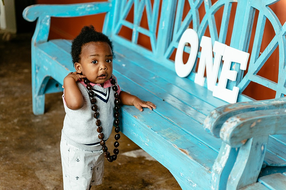 Little boy standing up against a baby blue bench with hawaiian bead necklace on with a white wooden ONE sign sitting on bench