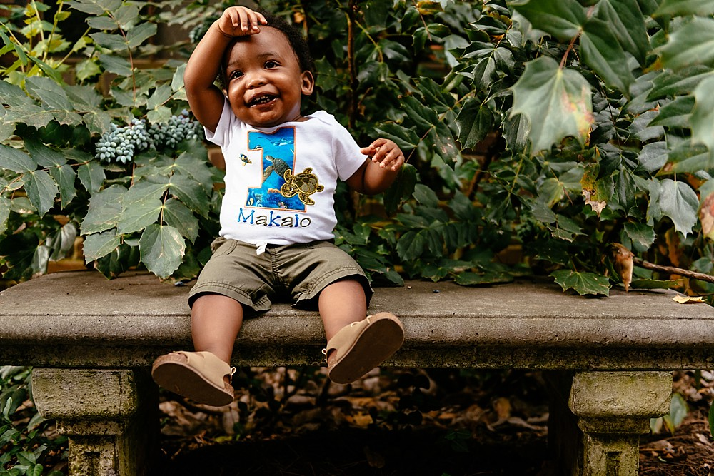 Little one year old wearing a custom made shirt with the number 1 and his name MAKAIO spelled on the shirt. He is sitting on a bench with greenery surrounding him.
