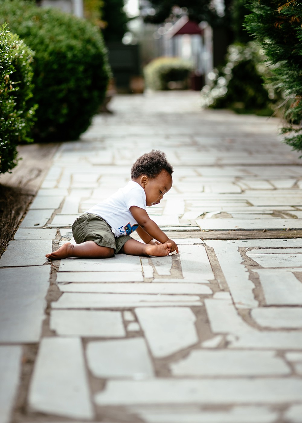 One year old using his hands to discover and explore the crevices on the cemented brick walkway