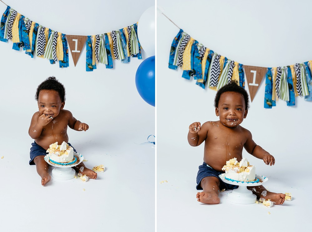 Baby having fun and making a mess of his personal cake.