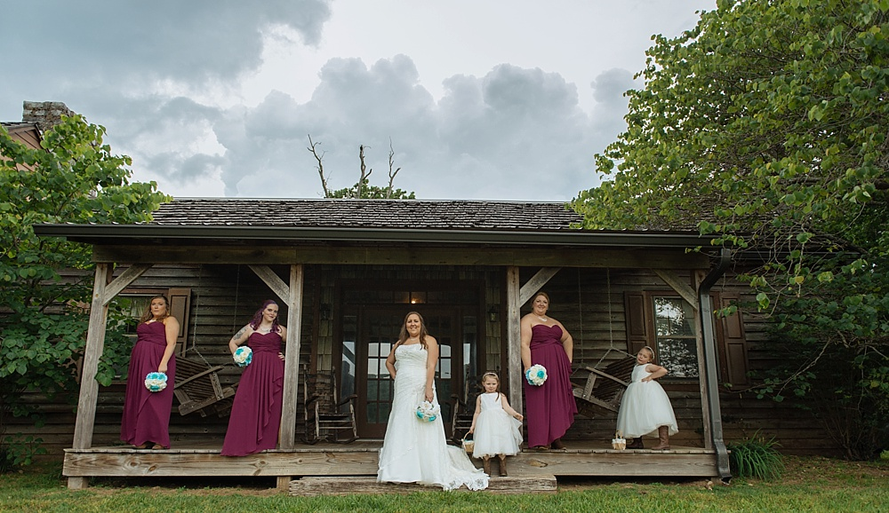 Gloomy clouds yet epic photo of bridesmaid on the cabin porch with flower girls