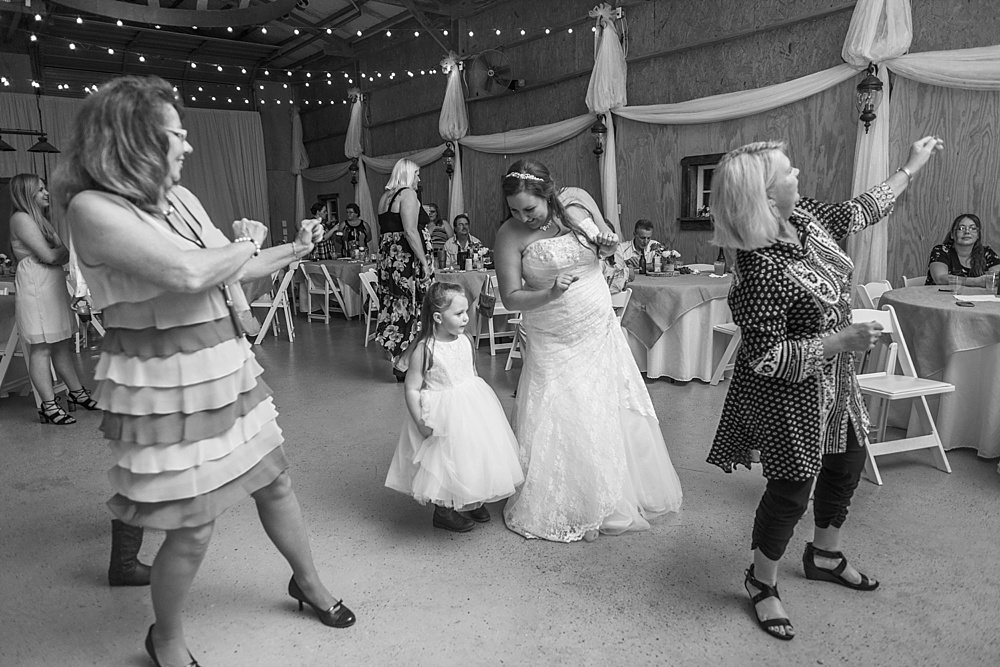 Bride dancing at reception with guests